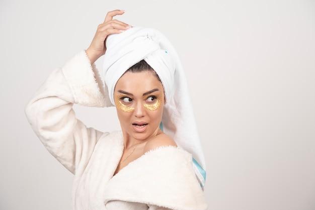 목욕 가운 및 화장품 눈 패치 포즈에서 젊은 여자.