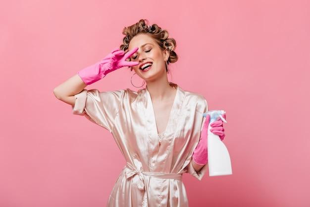 バスローブとゴム手袋の若い女性はピースサインを示し、洗剤を保持します