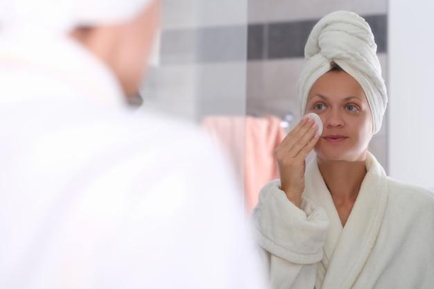 Молодая женщина в халате и полотенце на голове смывает косметику с лица перед зеркалом