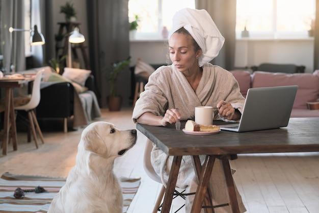 Молодая женщина в халате завтракает на рабочем месте и разговаривает со своей собакой в комнате