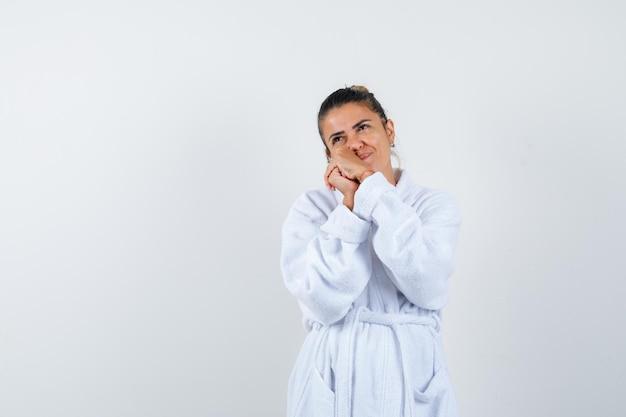 手に頬をもたれ、物思いにふけるバスローブを着た若い女性