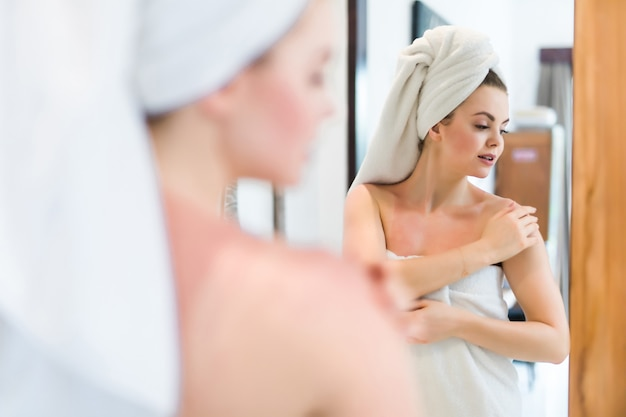 집에서 욕실 거울을보고 목욕 가운에 젊은 여자