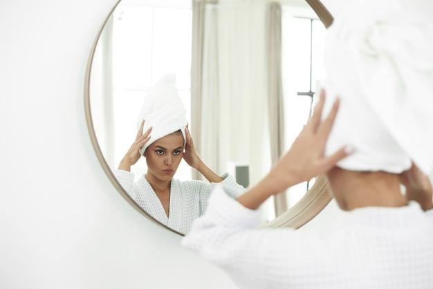 욕실 거울을보고 목욕 가운에 젊은 여자. 순수한 아름다움. 그녀의 얼굴을 만지고 거울을 보면서 웃 고 매력적인 여자.