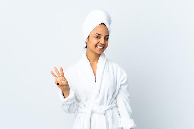 격리 된 흰 벽 위에 목욕 가운에 젊은 여자가 행복하고 손가락으로 세 세
