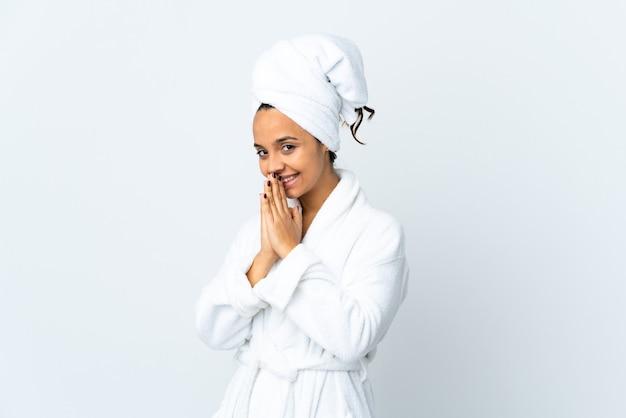 격리 된 흰 벽 위에 목욕 가운에 젊은 여자는 함께 손바닥을 유지합니다. 사람이 무언가를 요구한다