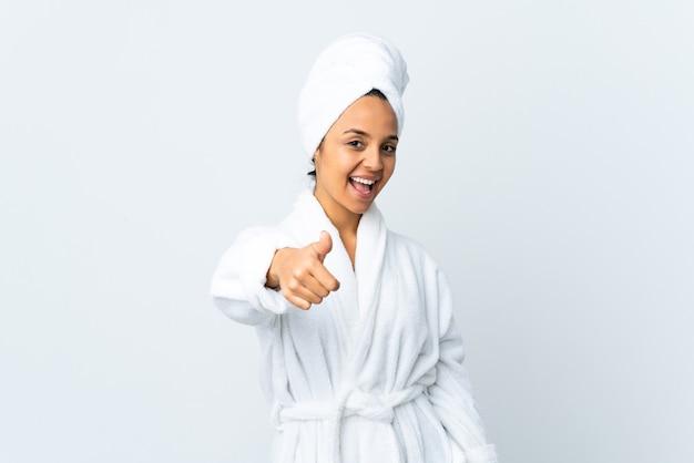 Молодая женщина в халате поверх изолированного белого с большими пальцами руки вверх, потому что произошло что-то хорошее