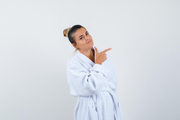 옆으로 가리키고 자신감을 찾고 목욕 가운에 젊은 여자