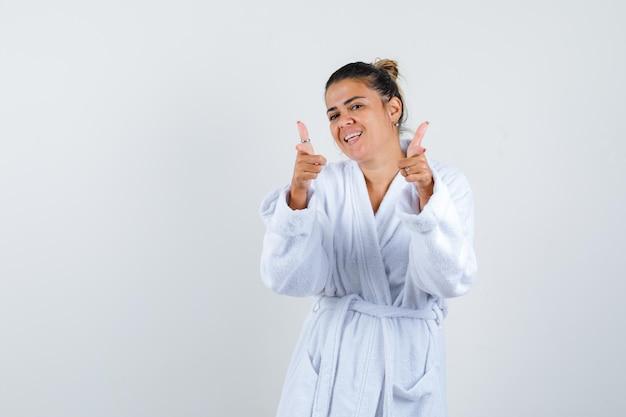 人差し指で指しているバスローブの若い女性
