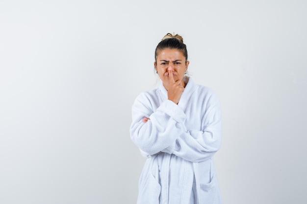 バスローブを着た若い女性が指で鼻を押して、面白そうに見える 無料写真