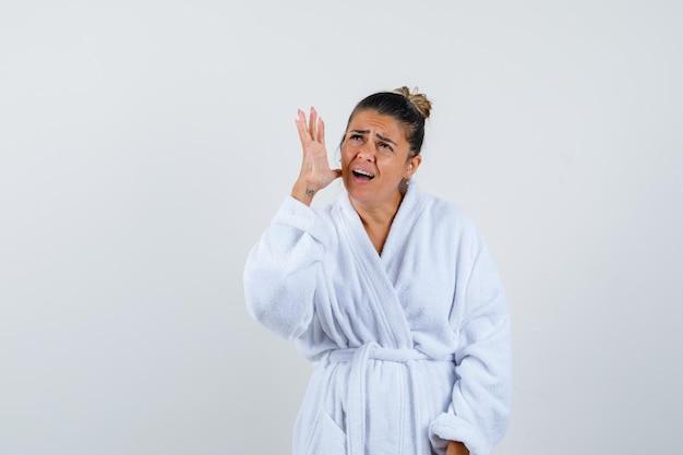 목욕 가운을 입은 젊은 여성이 무언가를 외치며 불안해 보인다