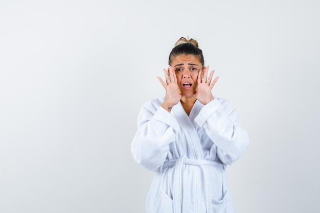 목욕 가운을 입은 젊은 여성이 무언가를 외치며 걱정스러운 표정을 짓고 있습니다.
