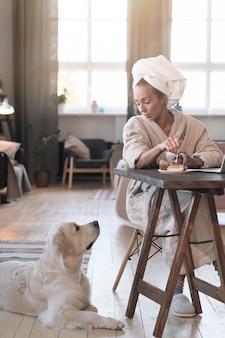 テーブルに座って、部屋で彼女の犬との会話中にコーヒーを飲むバスローブを着た若い女性