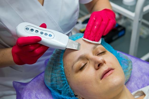超音波ピーリングと洗顔手順を行う美容院の若い女性。閉じる。