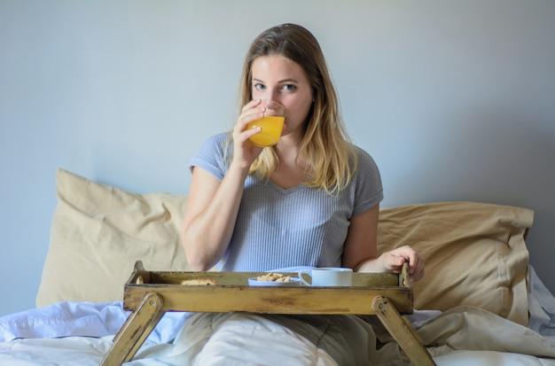 朝食を食べるベッドで若い女性