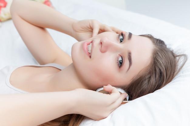 ヘッドフォンで音楽を聴くベッドで若い女性