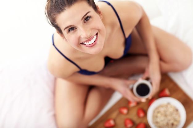 朝食とスマートフォンでベッドにいる若い女性