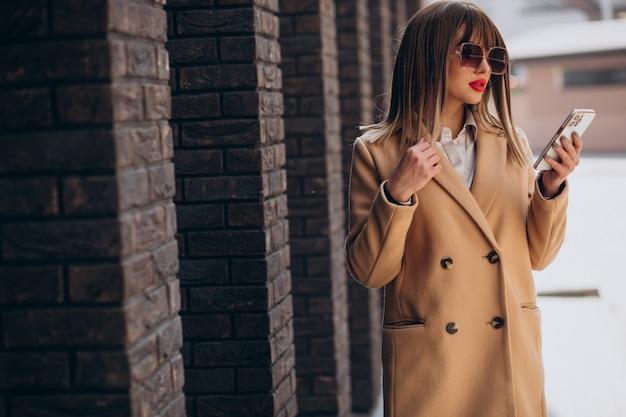 通りで電話を使うベージュのコートを着た若い女性