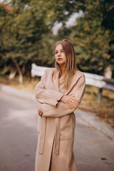 Молодая женщина в бежевом пальто гуляет в парке