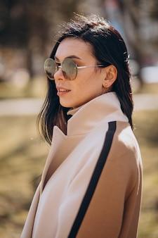 通りを歩くベージュのコートを着た若い女性
