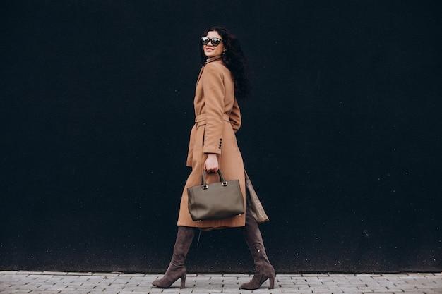 黒い壁の背景に屋外を歩くベージュのコートを着た若い女性