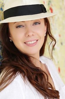 Молодая женщина в бежевой шляпе и летних нарядах
