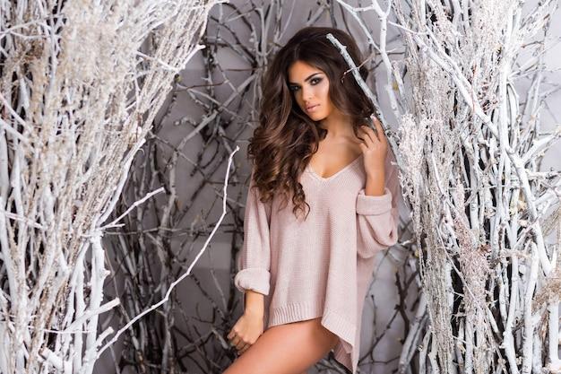 装飾されたスタジオの冬の森でポーズをとって大きなピンクのニットセーターの若い女性