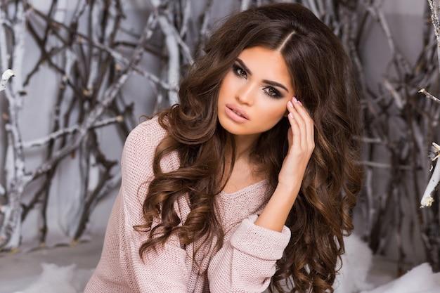 장식 된 스튜디오 겨울 숲에서 포즈 큰 분홍색 니트 스웨터에 젊은 여자