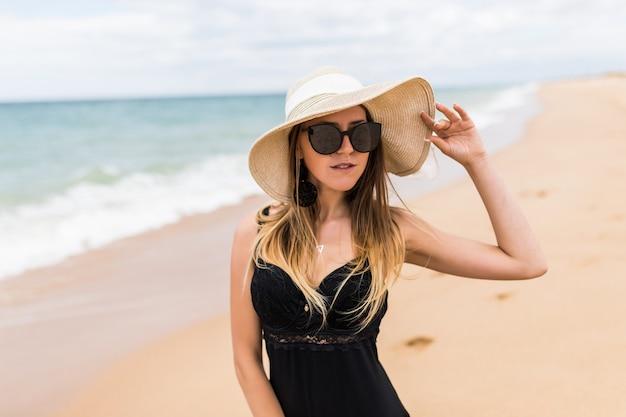 日当たりの良いビーチでリラックスしたビキニと日よけ帽の若い女性。