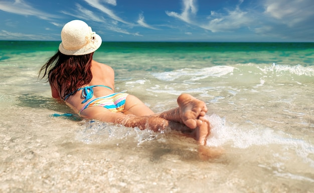 水の中のビーチに横たわって、ビーチで海の女性の遠くに見えるビキニの若い女性