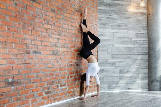 검은 색과 흰색 스포츠 옷을 입고 젊은 여자는 체육관에서 벽에 뻗어