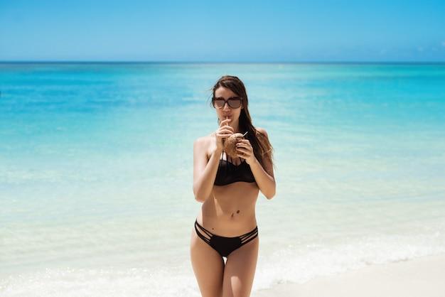 Молодая женщина в черном бикини пьет кокосовые коктейли на изумительном пляже