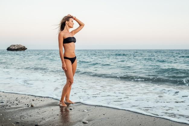 Молодая женщина в черном бикини на пляже вечером с морем и скалой