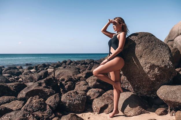 Молодая женщина в черном бикини стоит на скале перед чистым голубым небом