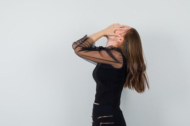 Молодая женщина в черной блузке и черных брюках закрывает лицо руками и выглядит с сожалением