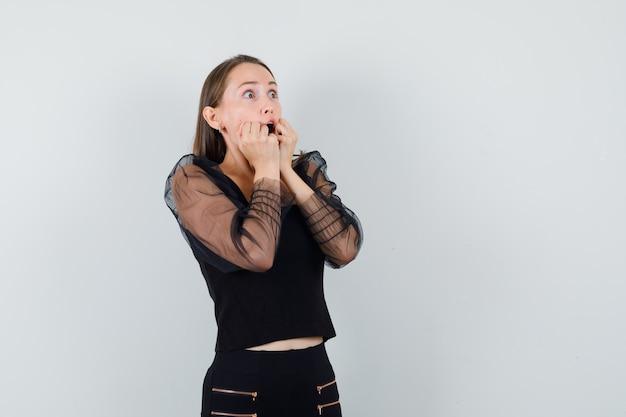 黒のブラウスと黒のズボンの若い女性が口の近くで手を握り、拳を握りしめ、驚いて見える、正面図。