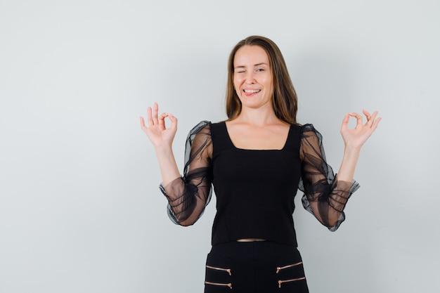 黒のブラウスと黒のズボンを着た若い女性が両手で大丈夫な兆候を示し、舌を突き出している