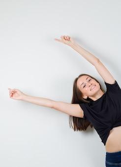 Молодая женщина в черной блузке показывает в сторону, протягивая руки и выглядит радостной