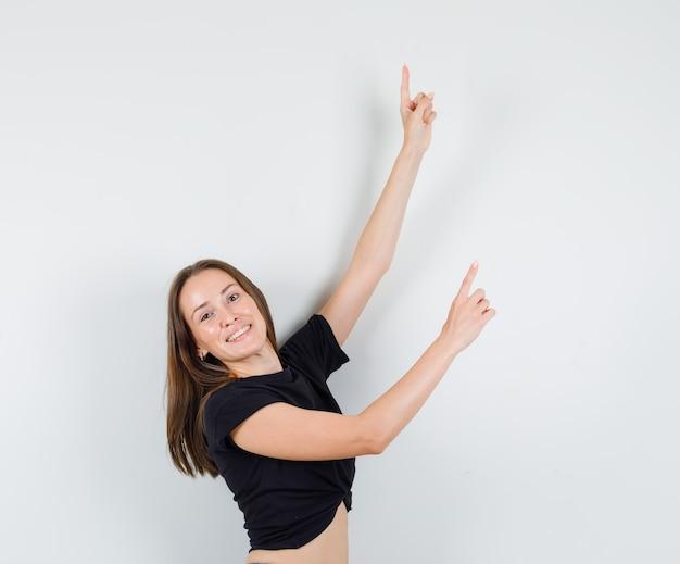Молодая женщина в черной блузке показывает в сторону, протягивая руки и выглядит позитивно
