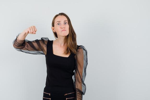 黒いブラウスを着た若い女性が拳を上げて攻撃的に見える