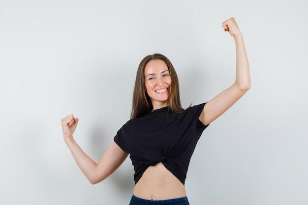 Молодая женщина в черной блузке протягивает руки и выглядит сильной