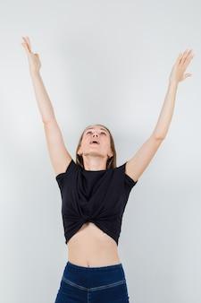 Молодая женщина в черной блузке протягивает руки, глядя вверх и выглядит счастливой