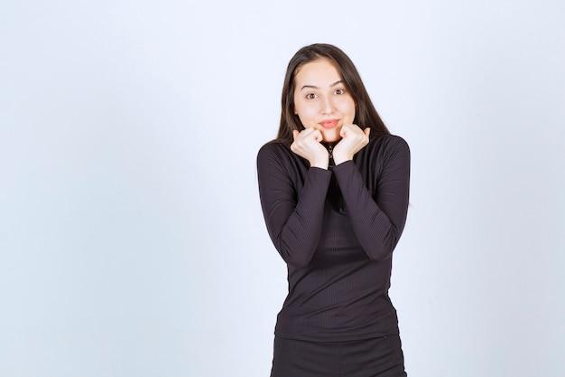 素敵なポーズを与える黒い服を着た若い女性