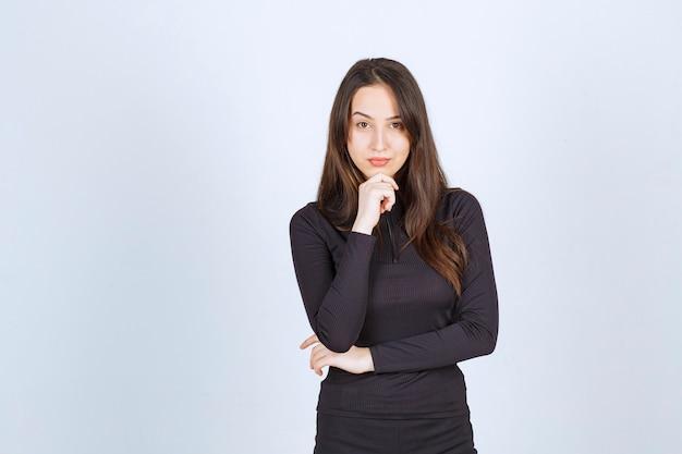 검은 옷을 입은 젊은 여성은 전문적이고 자신감이 있습니다.