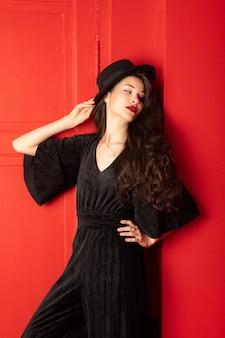 검은 드레스와 모자 스탠드에 젊은 여자