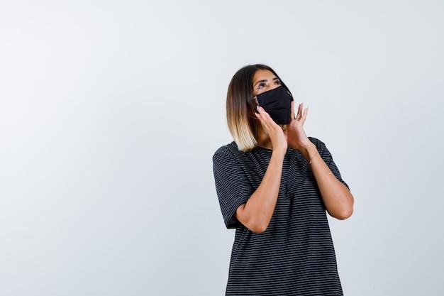 Молодая женщина в черном платье, черная маска, держась за руки возле рта, чтобы позвонить кому-то и смотреть сосредоточенно, вид спереди.