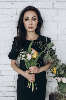 Young woman in black dress poses with colorful flowers before a white wall