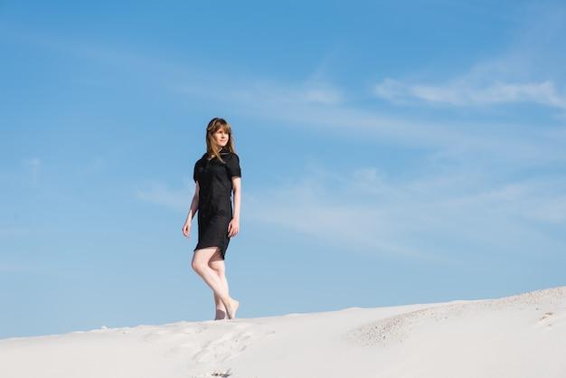 검은 드레스에 젊은 여자는 모래 언덕에서 산책