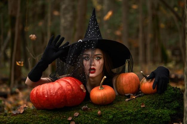 Молодая женщина в черном платье с шляпой ведьмы и оранжевой тыквой размещена вокруг в лесу, концепции хэллоуина. тема ужасов.