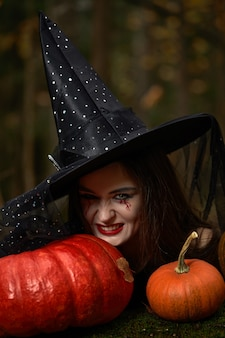 Молодая женщина в черном платье с шляпой ведьмы и оранжевой тыквой в лесу, концепция хэллоуина