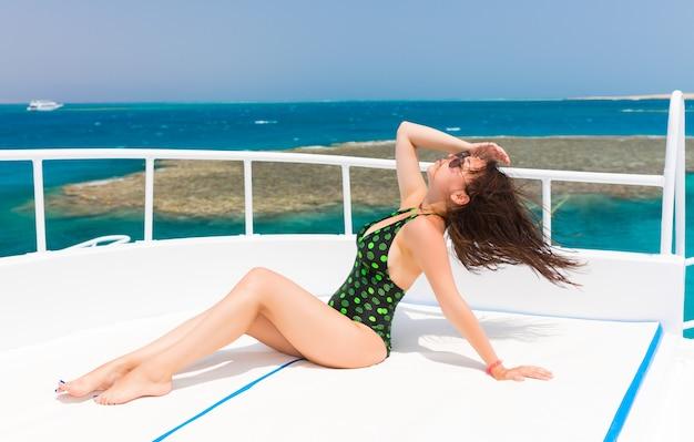 晴れた夏の日にヨットのデッキに横たわっている黒緑色の水着の若い女性、そよ風の発達する髪、背景の美しい海